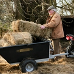 Man loading bales on to an ATV/Quad bike trailer