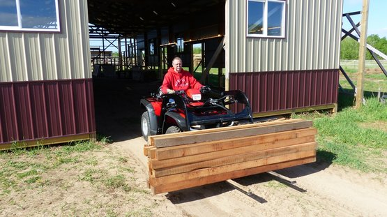 atv hydraulic loader with forklift attachment moving timber