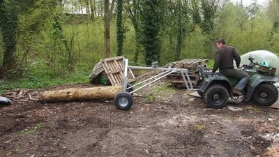 timber log arch towed by quad bike