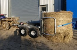 atv bale trailer holding a round bale of hay