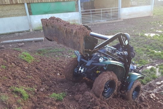 ATV front loader climbing up loaded with muck